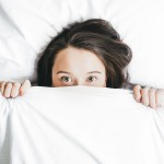 Woman laying in bed, hiding the bottom of her face with a white bedsheet.