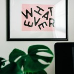 Word whatever in a frame on a wall, above a plant and black screen.