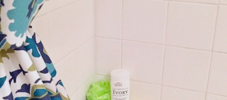 Shown: Multi-colored shower curtain opened to show two bath sponges in blue and green, an Ivory Body wash, and a lit tea light, on tub shelf.