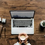 On a wooden table, two hands holding a coffee mug, a laptop, iPhone, pen, small plant and the word D R E A M. Photo Credit: rawpixel on UnSplash.