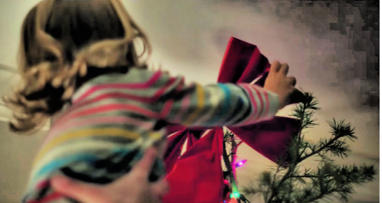 Little girl putting a star on the top of a Christmas tree.